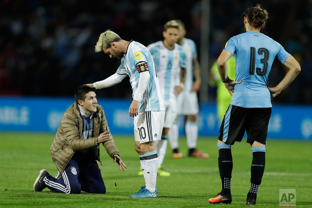 In this Sept. 1, 2016 photo, a fan who invaded the pitch kneels in front of Argentina's Lionel Messi, center, as Uruguay's Gaston Silva looks on during a 2018 World Cup qualifying soccer match in Mendoza, Argentina. Argentina won the match 1-0. (AP Photo/Victor R. Caivano)