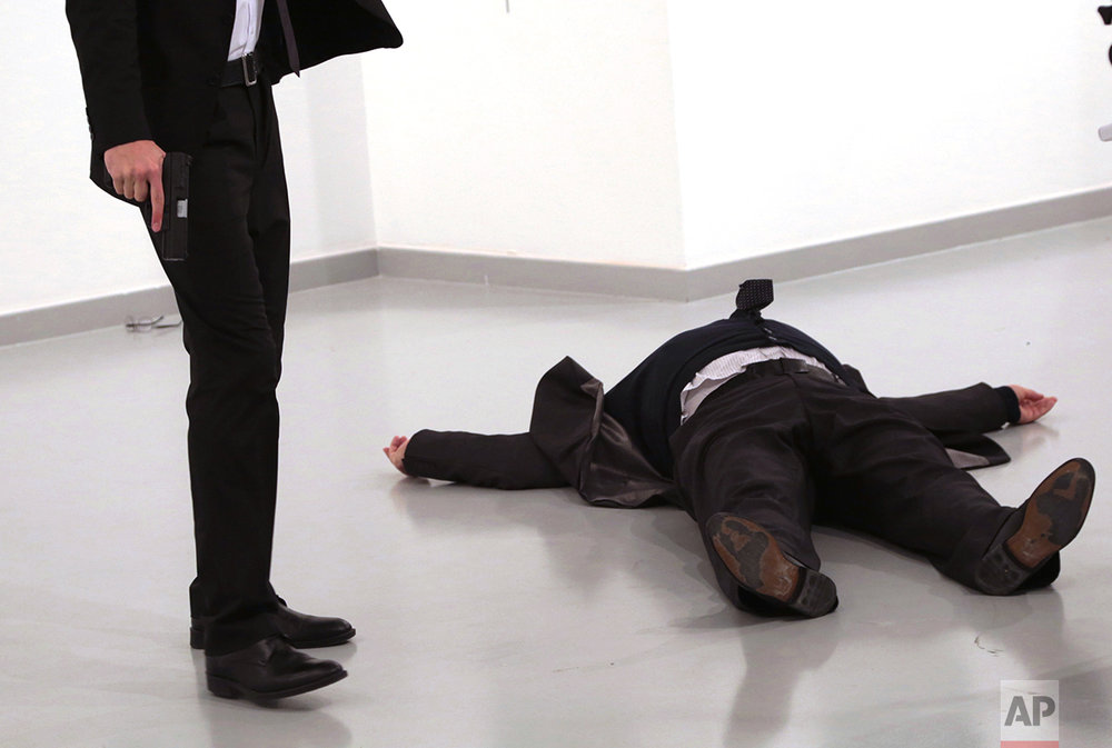 A man identified as Mevlut Mert Altintas holds the gun after shooting the Russian Ambassador to Turkey, Andrei Karlov, at a photo gallery in Ankara, Turkey, Monday, Dec. 19, 2016. A gunman opened fire on Russia's ambassador to Turkey at a photo exhibition on Monday. The Russian foreign ministry spokeswoman said he was hospitalized with a gunshot wound. (AP Photo/Burhan Ozbilici)