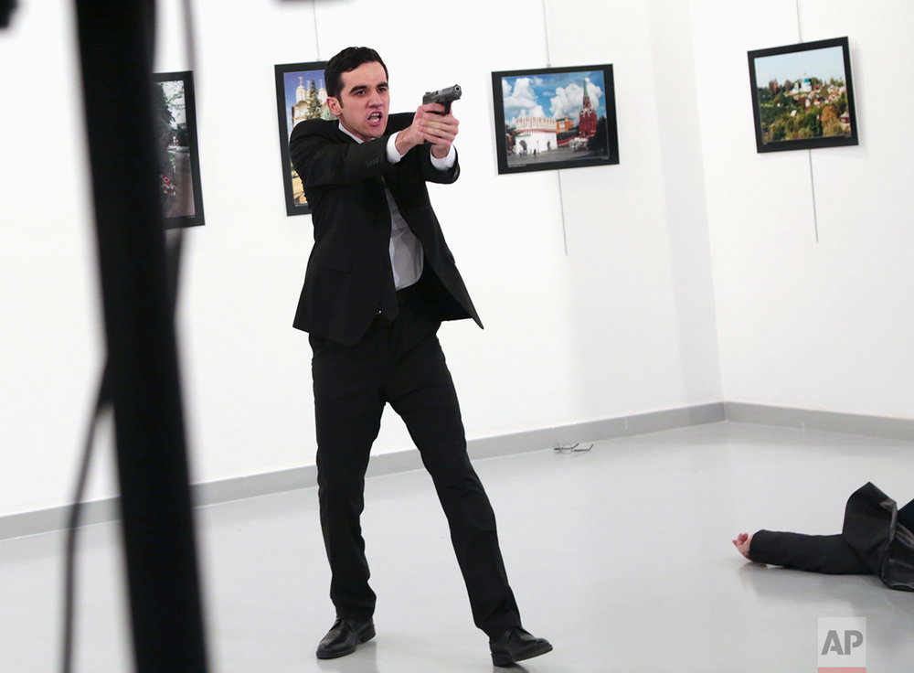 A man identified as Mevlut Mert Altintas gestures after shooting Andrei Karlov, the Russian Ambassador to Turkey, on the floor, at a photo gallery in Ankara, Turkey, Monday, Dec. 19, 2016. (AP Photo/Burhan Ozbilici)