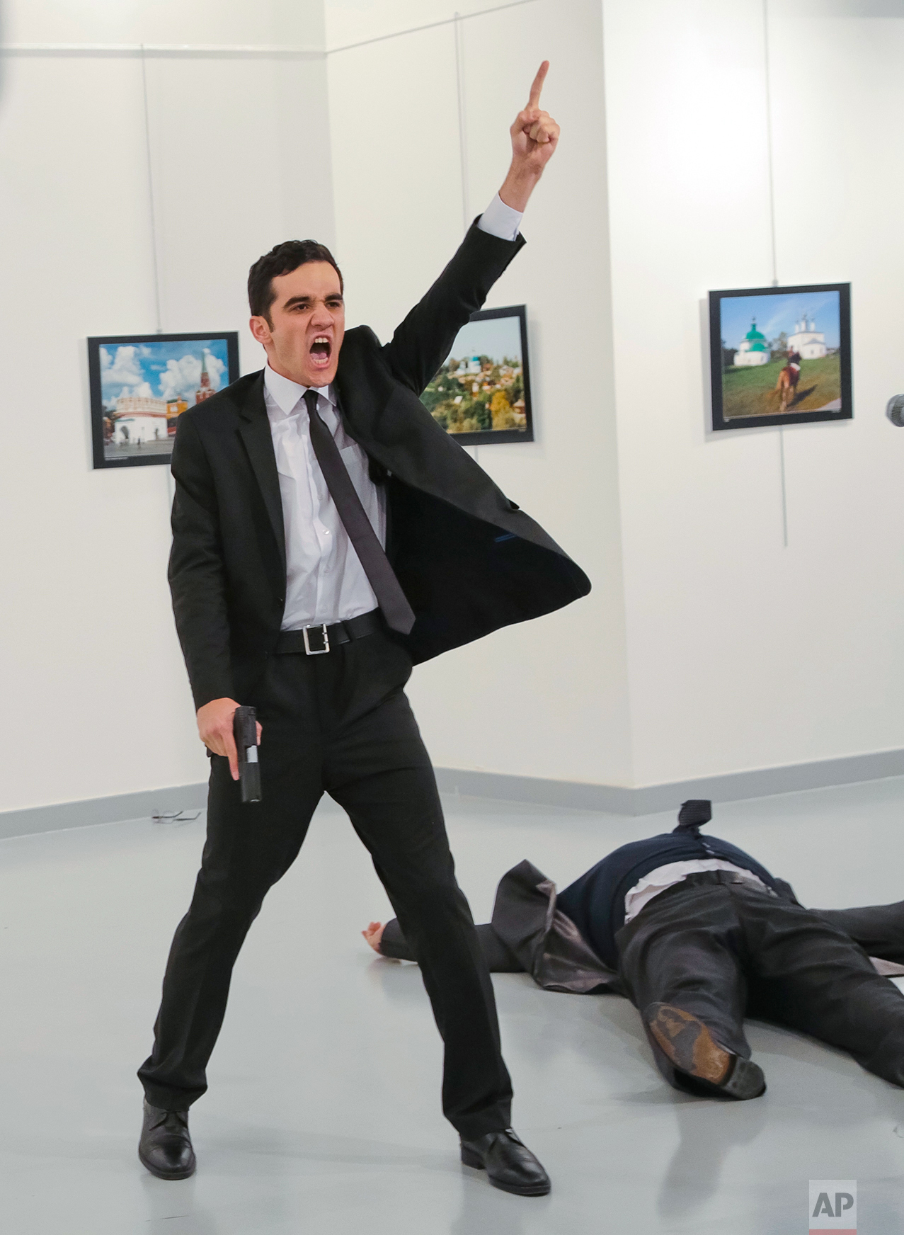 """A man identified as Mevlut Mert Altintas holds up a gun after shooting Andrei Karlov, the Russian Ambassador to Turkey, at a photo gallery in Ankara, Turkey, Monday, Dec. 19, 2016. Shouting """"Don't forget Aleppo! Don't forget Syria!"""" Altintas fatally shot Karlov in front of stunned onlookers at a photo exhibit. Police killed the assailant after a shootout. (AP Photo/Burhan Ozbilici)"""