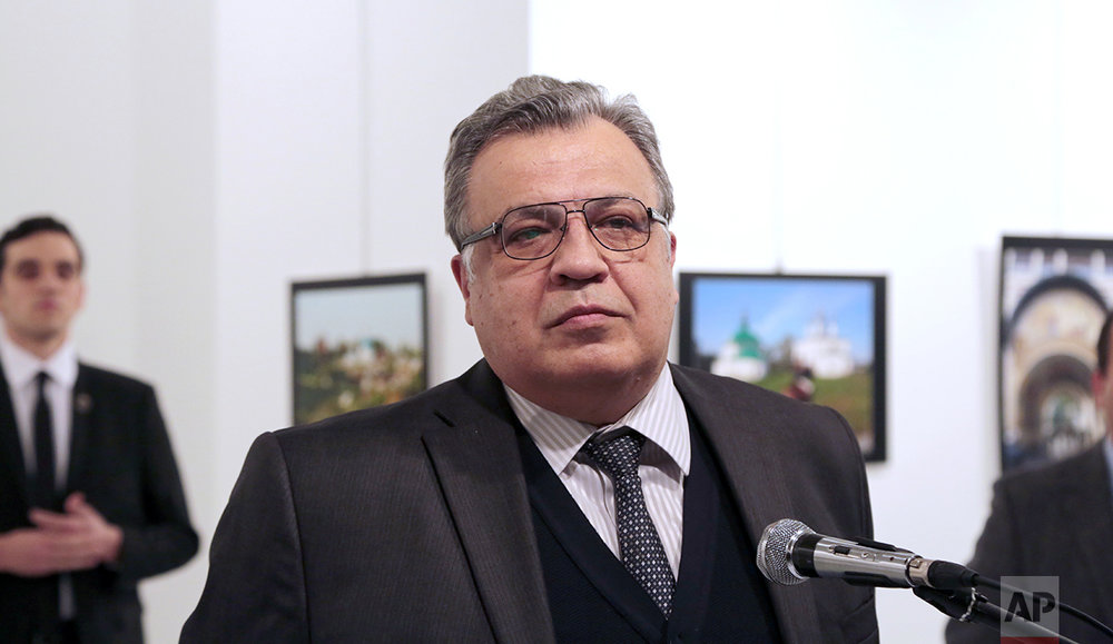 Andrei Karlov, the Russian Ambassador to Turkey, speaks at a photo exhibition in Ankara on Monday, Dec. 19, 2016, moments before a gunman opened fire on him. Karlov was rushed to a hospital after the attack and later died from his gunshot wounds. The gunman is seen at rear on the left. (AP Photo/Burhan Ozbilici)