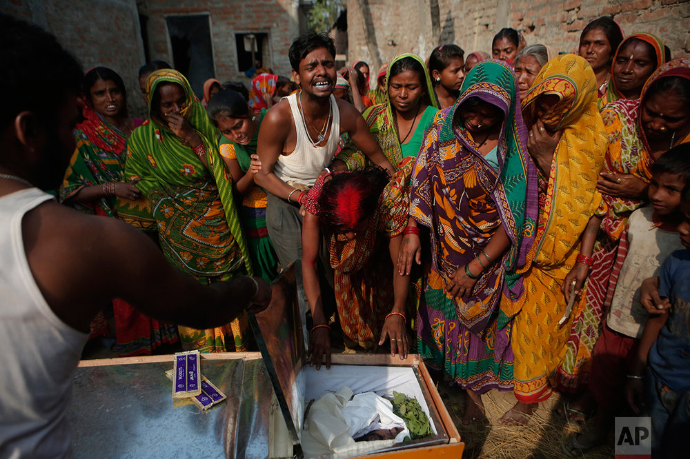 In this Wednesday, Nov. 23, 2016 photo, Saro Kumari Mandal, 26, cries as she leans on the coffin carrying her husband Balkisun Mandal Khatwe, 26, a migrant worker who died in his sleep in Qatar, at Belhi village, in Saptari district, Nepal. The number of Nepali workers going abroad has more than doubled since the country began promoting foreign labor in recent years: from about 220,000 in 2008 to about 500,000 in 2015. Yet the number of deaths among those workers has risen much faster in the same period. But now medical researchers say these deaths fit a familiar pattern: Every decade or so, dozens, or even hundreds, of seemingly healthy Asian men working abroad in poor conditions start dying in their sleep. The suspected killer even has a name: Sudden Unexplained Nocturnal Death Syndrome. (AP Photo/Niranjan Shrestha)