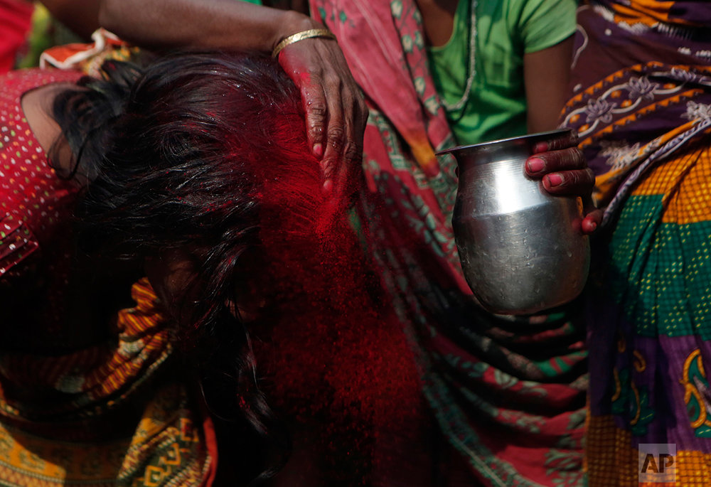 In this Wednesday, Nov. 23, 2016 photo, family members rinse out the red tikka powder, which is only allowed for married women, from the forehead of Saro Kumari Mandal, 26, after the death of her husband Balkisun Mandal Khatwe, 26, at Belhi village, in Saptari district, Nepal. Balkisun died in his sleep in Qatar, where he was working for Habtoor Leighton Group, loading trucks to build new highways. The number of Nepali workers going abroad has more than doubled since the country began promoting foreign labor in recent years: from about 220,000 in 2008 to about 500,000 in 2015. Yet the number of deaths among those workers has risen much faster in the same period. In total, over 5,000 workers from this small country have died working abroad since 2008, more than the number of U.S. troops killed in the Iraq War. (AP Photo/Niranjan Shrestha)
