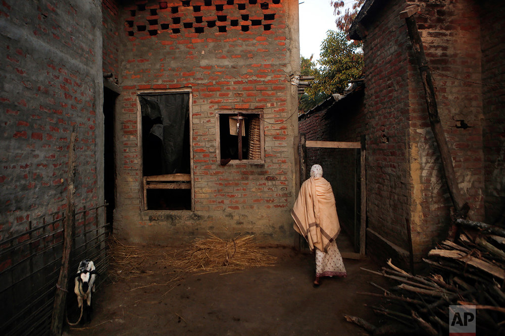 In this Wednesday, Nov. 30, 2016 photo, Saro Kumari Mandal, 26, whose husband died in his sleep as a migrant worker in Qatar, walks dressed in a white sari inside her home in Belhi village, Saptari district of Nepal. The number of Nepali workers going abroad has more than doubled since the country began promoting foreign labor in recent years: from about 220,000 in 2008 to about 500,000 in 2015. Yet the number of deaths among those workers has risen much faster in the same period. In total, over 5,000 workers from this small country have died working abroad since 2008, more than the number of U.S. troops killed in the Iraq War. Saro isn't allowed to remarry and will probably live on the edges of society, earning nothing more than some food to eat and a place to sleep. (AP Photo/Niranjan Shrestha)