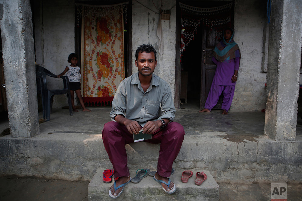 "In this Nov. 23, 2016 photo, Mohammed Tohit, 28, holds his passport in front of the solid, cement and plaster home that he built for his family in Belhi Village, Nepal. Tohit is the envy and inspiration of the village. He worked in Malaysia for almost six years sewing clothes for Nike, Lacoste and Columbia Sportswear, saving more than $20,000, enough to build the sturdy two-bedroom house. ""I am scared, sure, but I have no way to earn anything here,"" he says. ""I have no choice but to leave again."" (AP Photo/Niranjan Shrestha)"