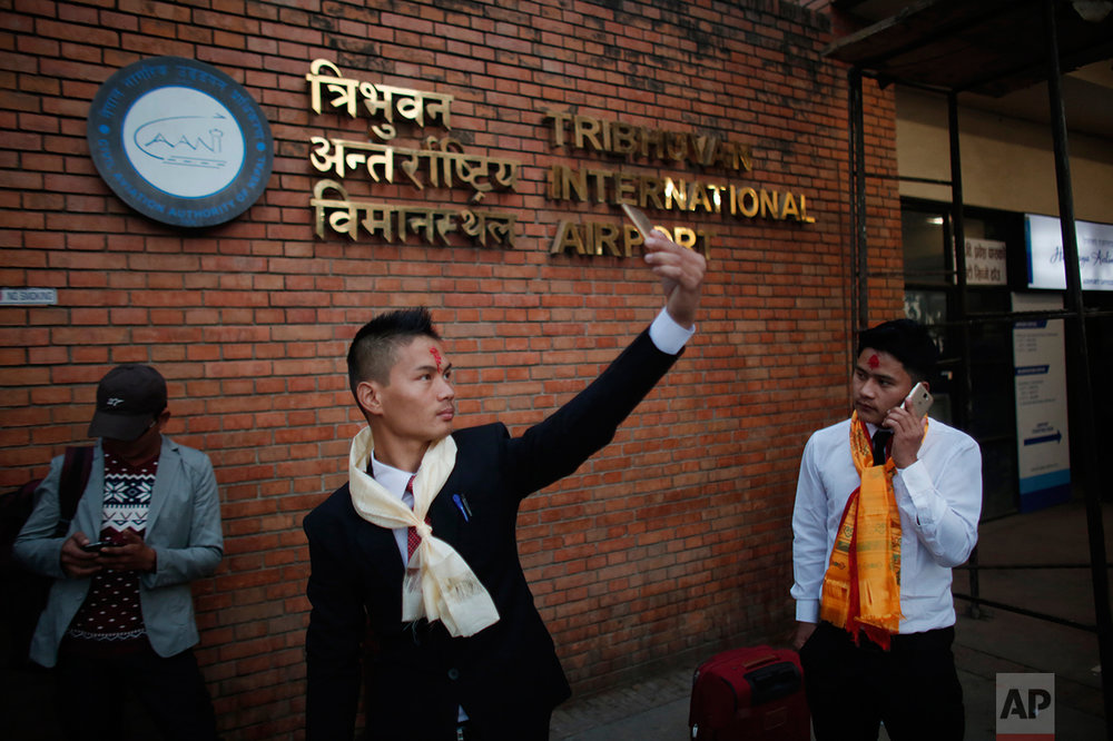 In this photo taken on Monday, Nov. 28, 2016, a Nepali Prem Bahadur Ale Magar, 23, takes a selfie while he waits for his flight to Malaysia, where he will work in a warehouse as a cleaner, at Tribhuwan International airport in Kathmandu, Nepal. The number of Nepali workers going abroad has more than doubled since the country began promoting foreign labor in recent years: from about 220,000 in 2008 to about 500,000 in 2015. The unskilled workers fill a host of global demands: building highways, stadiums and houses in Gulf states and guarding shopping malls, sewing sweatshirts and assembling televisions in Malaysia. (AP Photo/Niranjan Shrestha)