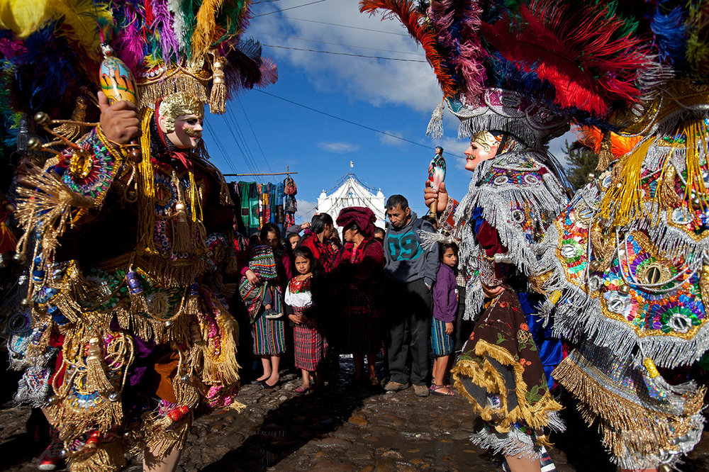 Masked dancers perform outside St. Thomas church during a celebration honoring the patron saint of Chichicastenango, Guatemala, Wednesday, Dec. 21, 2016. (AP Photo/Moises Castillo)