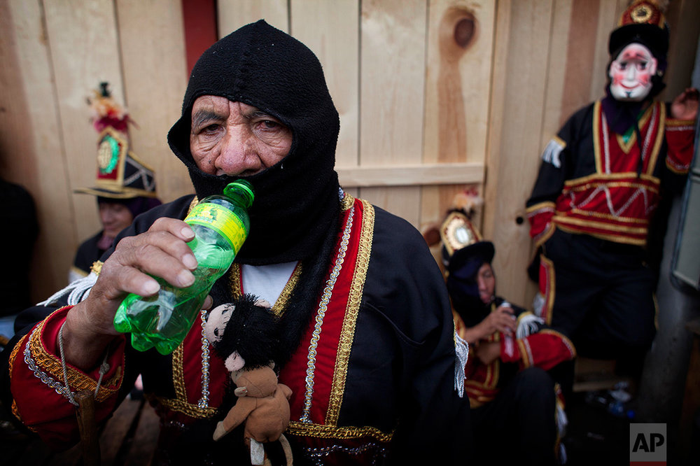 A dancer drinks water as he rests during celebrations honoring Saint Thomas, the patron saint of Chichicastenango, Guatemala, Wednesday, Dec. 21, 2016. (AP Photo/Moises Castillo)