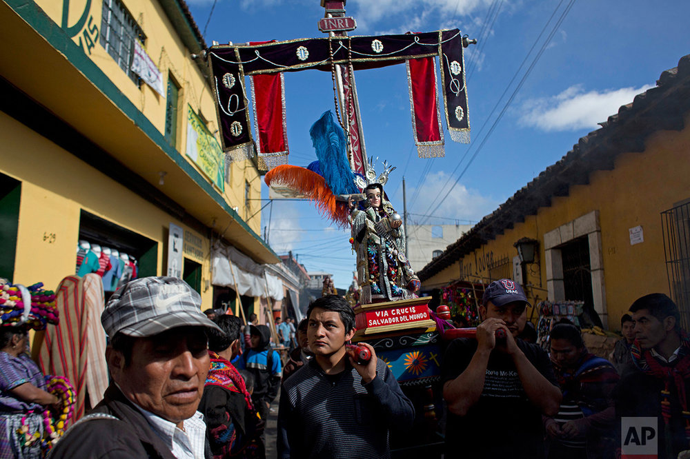 Men carry a religious statue during a procession in honor of Saint Thomas, the patron saint of Chichicastenango, Guatemala, Wednesday, Dec. 21, 2016. (AP Photo/Moises Castillo)