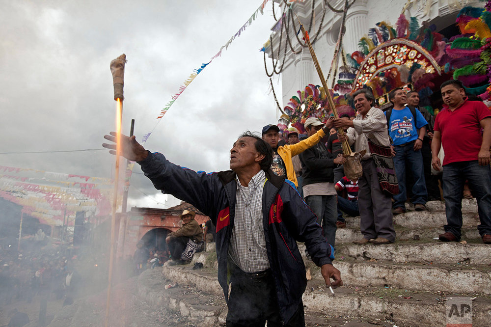A man launches a firecracker during a celebration honoring Saint Thomas, the patron saint of Chichicastenango, Guatemala, Wednesday, Dec. 21, 2016.  (AP Photo/Moises Castillo)