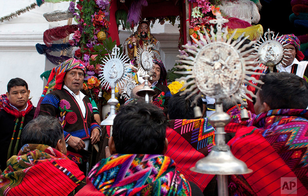 Members of a brotherhood pray after a procession in honor of Saint Thomas, the patron saint of Chichicastenango, Guatemala, Wednesday, Dec. 21, 2016. (AP Photo/Moises Castillo)