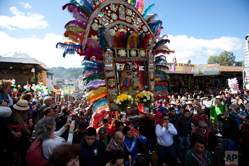 Men carry an elaborate statue of Saint Thomas during a celebration honoring the patron saint of Chichicastenango, Guatemala, Wednesday, Dec. 21, 2016. (AP Photo/Moises Castillo)