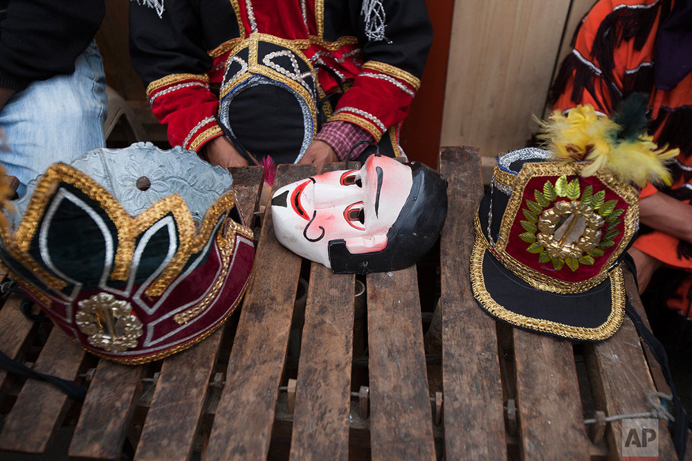 A costume mask and hats sit on a marimba instrument during a break at celebrations honoring Saint Thomas, the patron saint of Chichicastenango, Guatemala, Wednesday, Dec. 21, 2016. (AP Photo/Moises Castillo)
