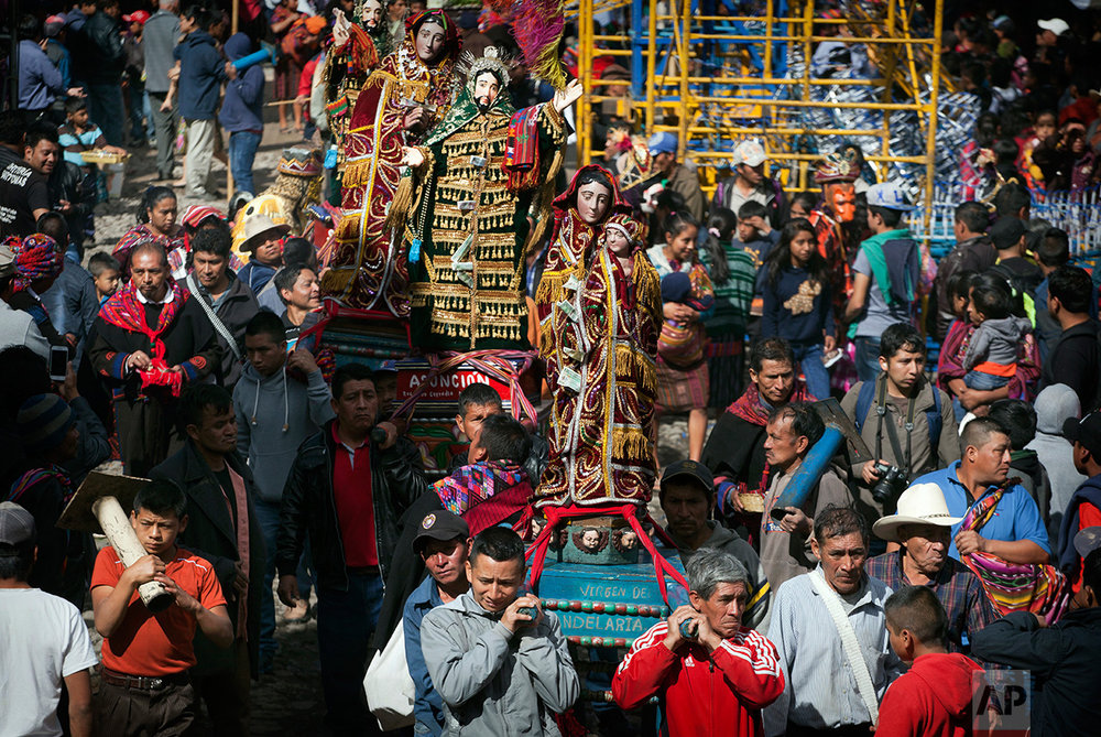 Men carry statues of different religious icons during a procession in honor of Saint Thomas, the patron saint of Chichicastenango, Guatemala, Wednesday, Dec. 21, 2016.  (AP Photo/Moises Castillo)