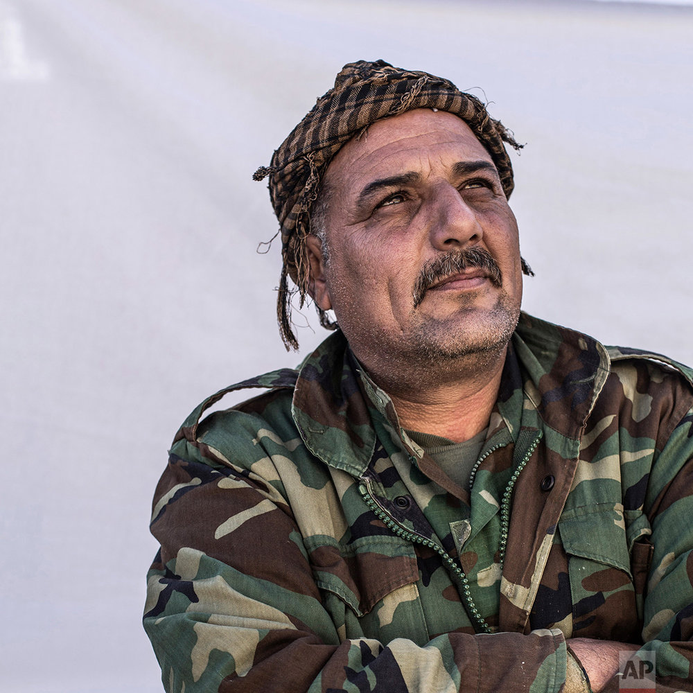Saad Faraq, 43, a Christian Peshmerga fighters poses for a portrait in the Karamlis complex, where Christians displaced by Islamic State militants are living, in Irbil, Iraq, Friday, Dec. 23, 2016. Iraq's Christians are marking the holiday in his camp for displaced people with a sense of worry and despair,  unable to return to their towns they were forced to flee two years ago by the Islamic State group's onslaught. (AP Photo/Manu Brabo)