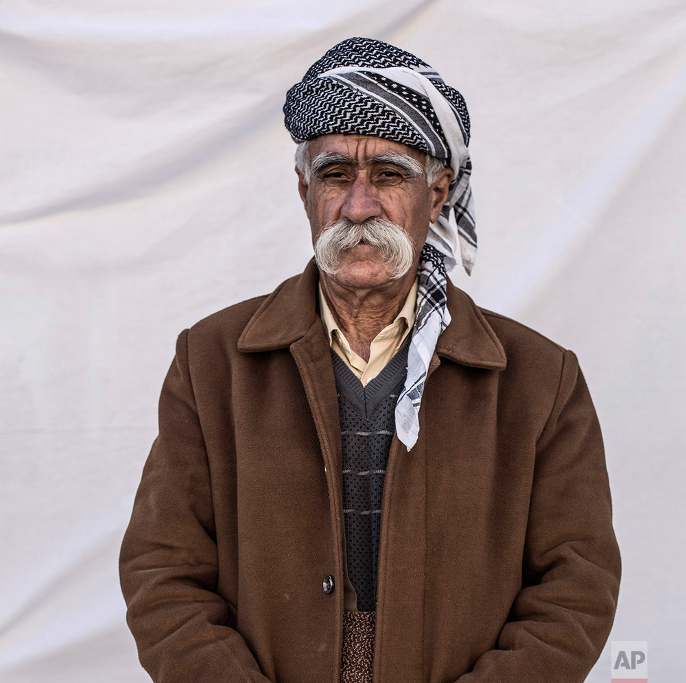 Hamid Khatab Jasm, 77, from Tal Al-Labnin poses for a portrait in the Karamlis complex, where Christians displaced by Islamic State militants are living, in Irbil, Iraq, Friday, Dec. 23, 2016. Iraq's Christians are marking the holiday in his camp for displaced people with a sense of worry and despair,  unable to return to their towns they were forced to flee two years ago by the Islamic State group's onslaught. (AP Photo/Manu Brabo)