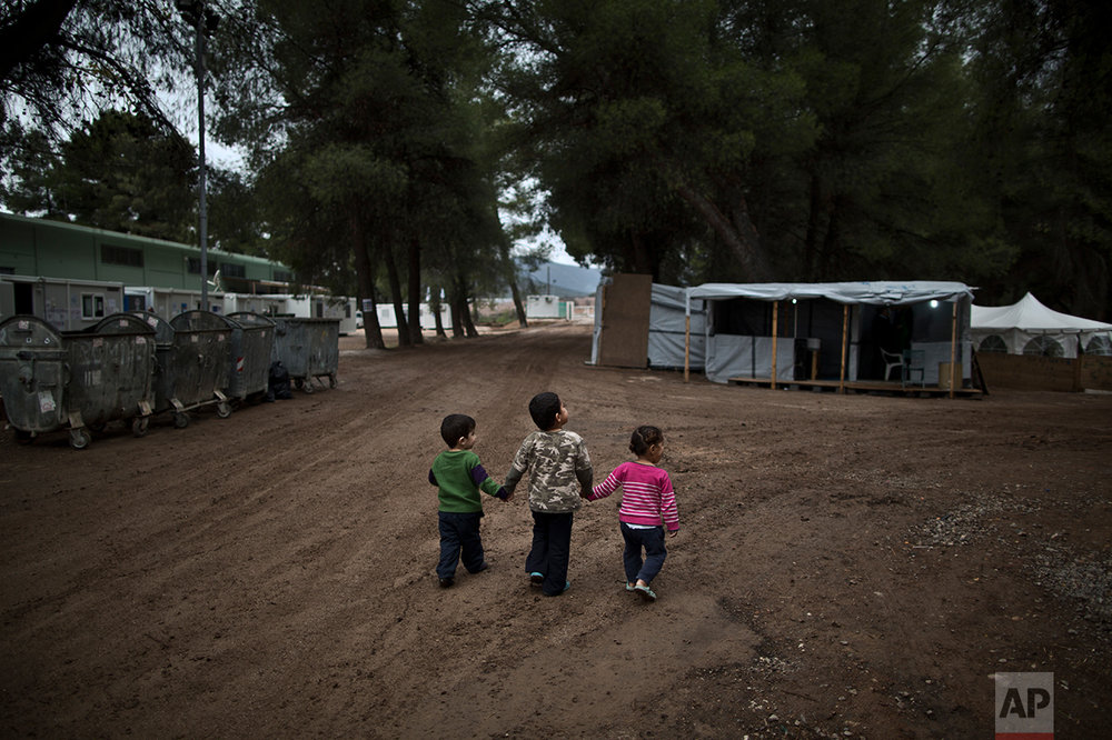 Syrian refugee children hold hands while walking in the refugee camp of Ritsona about 86 kilometers (53 miles) north of Athens, Wednesday, Dec. 28, 2016.  (AP Photo/Muhammed Muheisen)