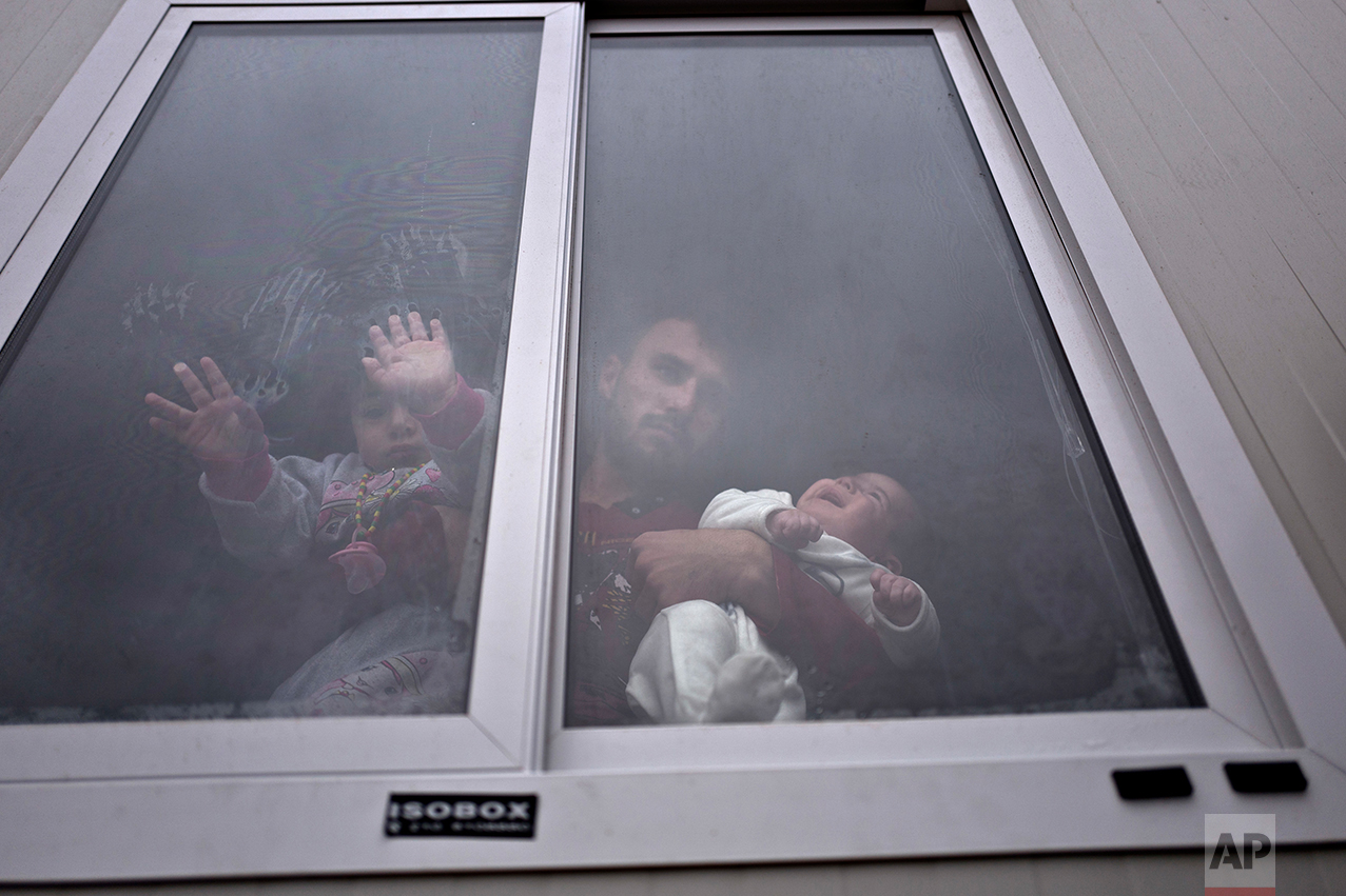 Refugee Siban Assad, 20 years old, from al-Hasaka, Syria, looks out the window of his shelter while holding his daughters, Ruba, one month, and Maldar, 1, at the refugee camp of Ritsona about 86 kilometers (53 miles) north of Athens, Wednesday, Dec. 28, 2016. (AP Photo/Muhammed Muheisen)