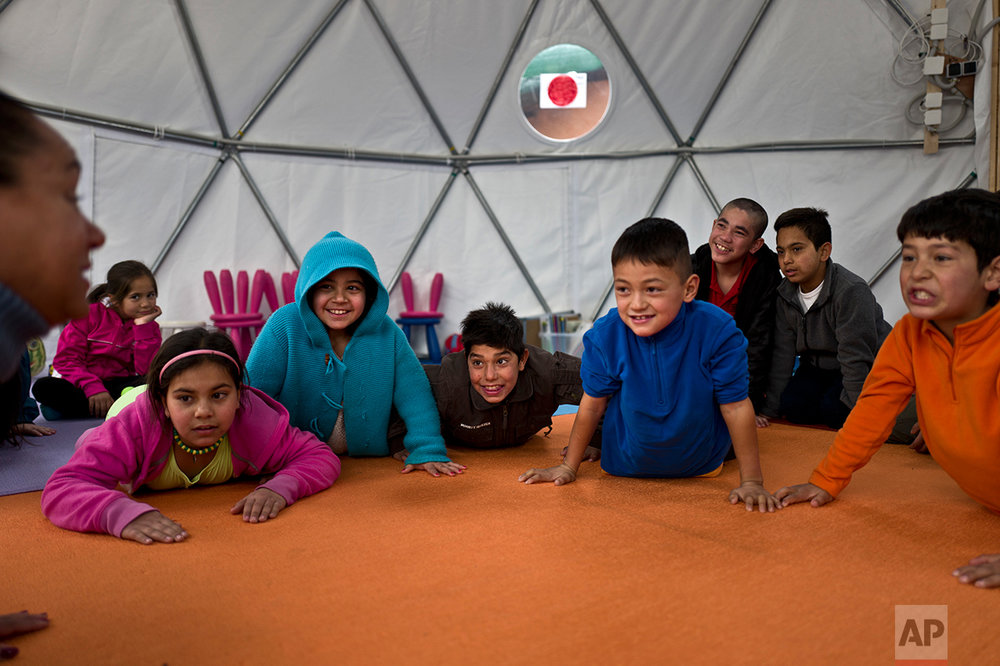 Afghan refugee children attend a yoga session during a class at a makeshift school in the refugee camp of Oinofyta about 58 kilometers (36 miles) north of Athens, Tuesday, Dec. 27, 2016. (AP Photo/Muhammed Muheisen)