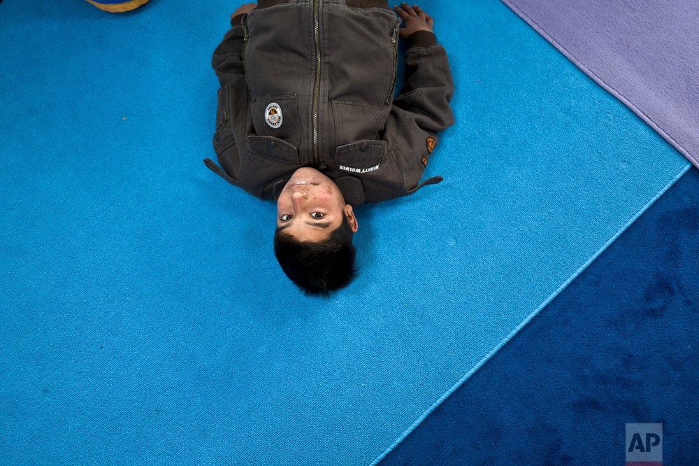 An Afghan refugee boy looks up while attending a yoga session during a class at a makeshift school in the refugee camp of Oinofyta about 58 kilometers (36 miles) north of Athens, Tuesday, Dec. 27, 2016. (AP Photo/Muhammed Muheisen)
