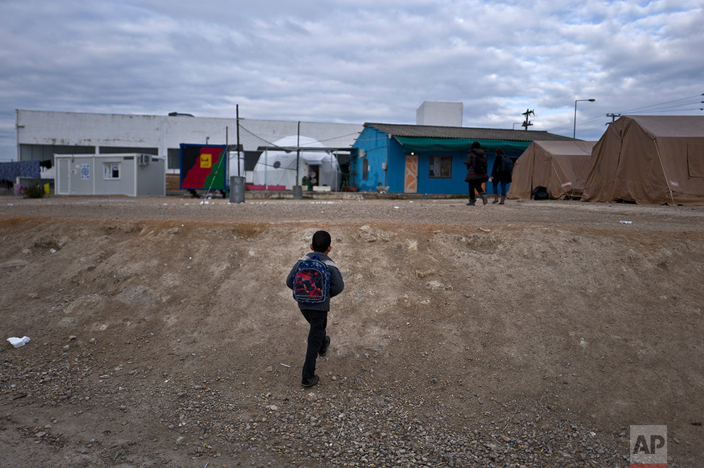 An Afghan refugee boy walks to attend a class at a makeshift school in the refugee camp of Oinofyta about 58 kilometers (36 miles) north of Athens, Tuesday, Dec. 27, 2016. (AP Photo/Muhammed Muheisen)