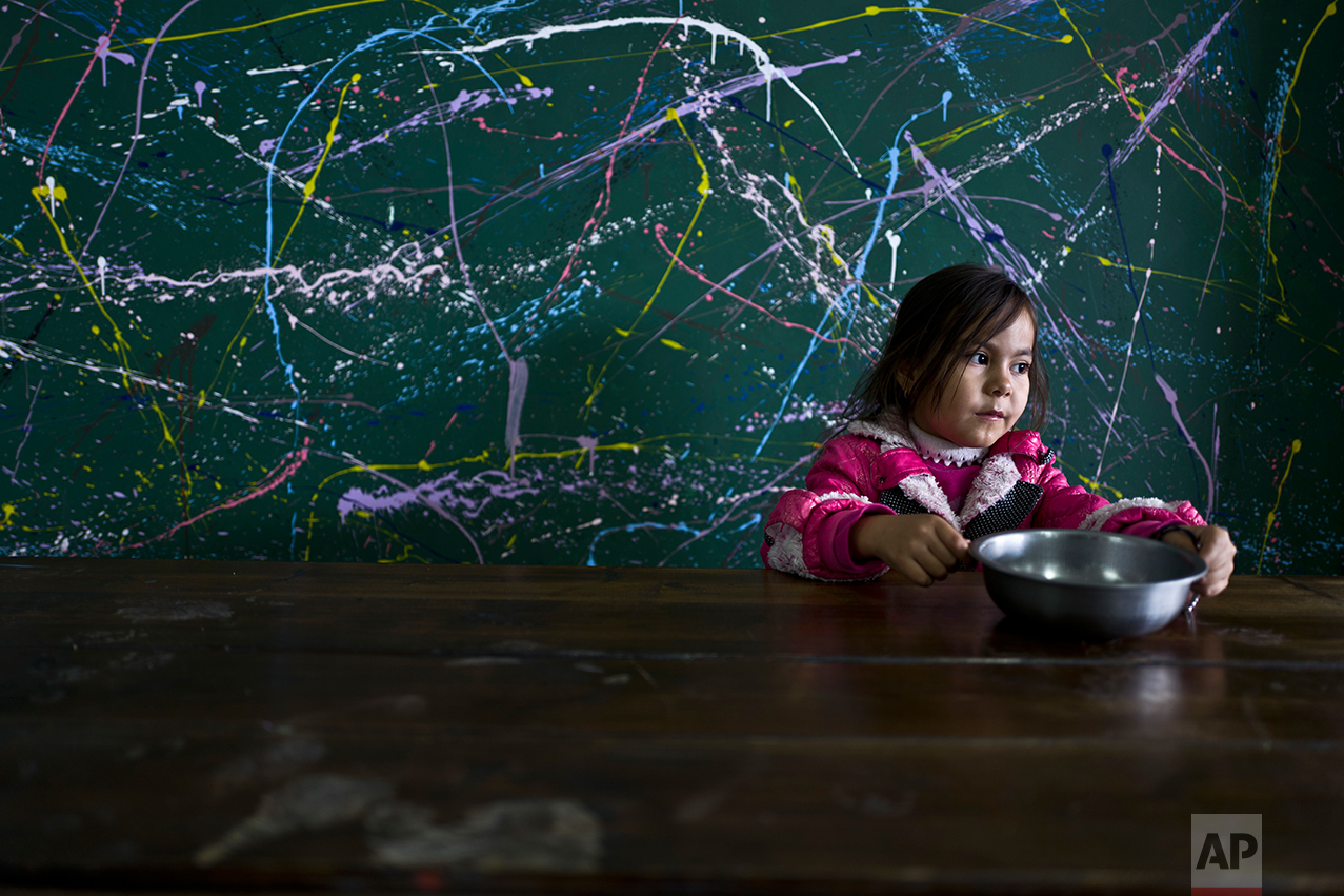 Afghan refugee Setayesh Hassan, 5, sits around a table after eating her lunch at the refugee camp of Oinofyta, about 58 kilometers (36 miles) north of Athens, Monday, Dec. 26, 2016. (AP Photo/Muhammed Muheisen)