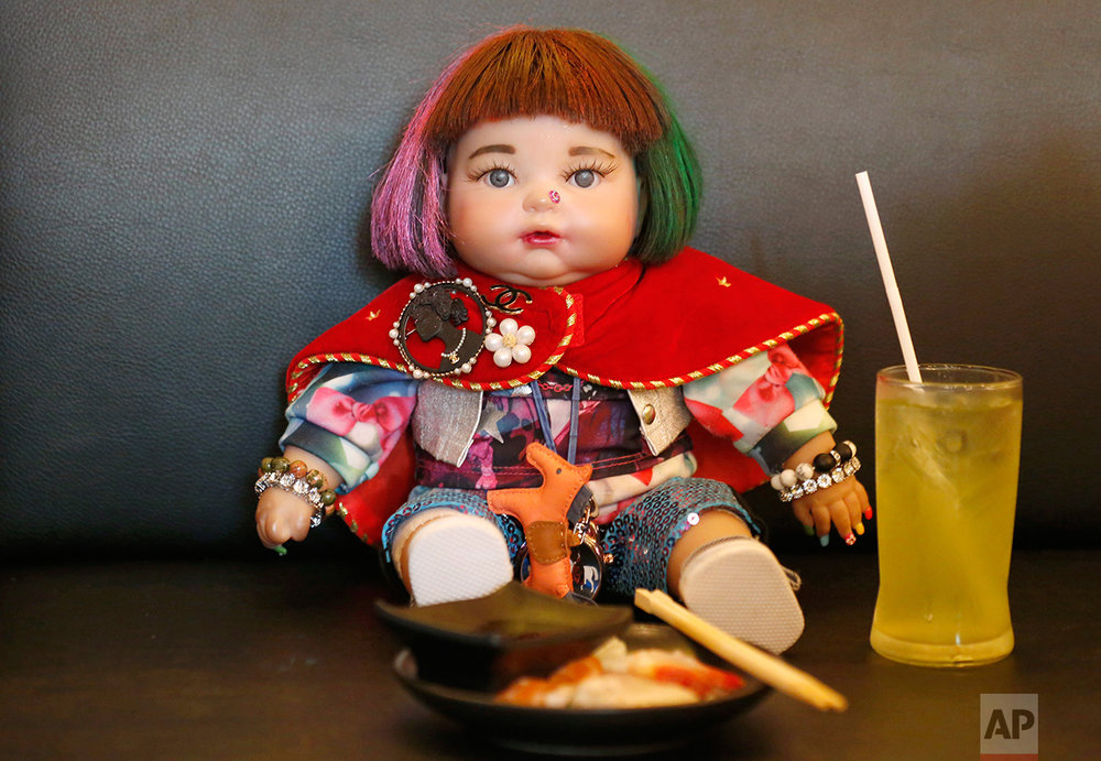 "In this Friday, Jan. 29, 2016 photo, a ""child angel"" doll is offered food by its owner Supavadee Tapmalai at a Japanese restaurant in Bangkok, Thailand. The dolls, which are said to bring good luck to their owners, became a media sensation after a leaked memo from a Thai budget airline gave pointers on how they could be treated like passengers if they have a paid-for seat. Thai people are superstitious, and the doll phenomenon has been analyzed as a modern version of a traditional totem containing real body parts, but as a fad it seems have more in common with Furby dolls. (AP Photo/Sakchai Lalit)"