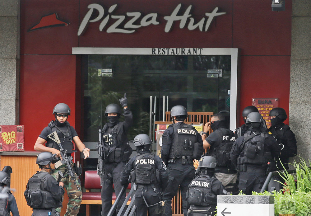 Police officers gather outside a Pizza Hut restaurant next door to a Starbucks cafe which was attacked in Jakarta, Indonesia Thursday, Jan. 14, 2016. Attackers set off explosions at a Starbucks cafe in a bustling shopping area in Indonesia's capital and waged gun battles with police Thursday, leaving bodies in the streets as office workers watched in terror from high-rise windows. (AP Photo/Achmad Ibrahim)