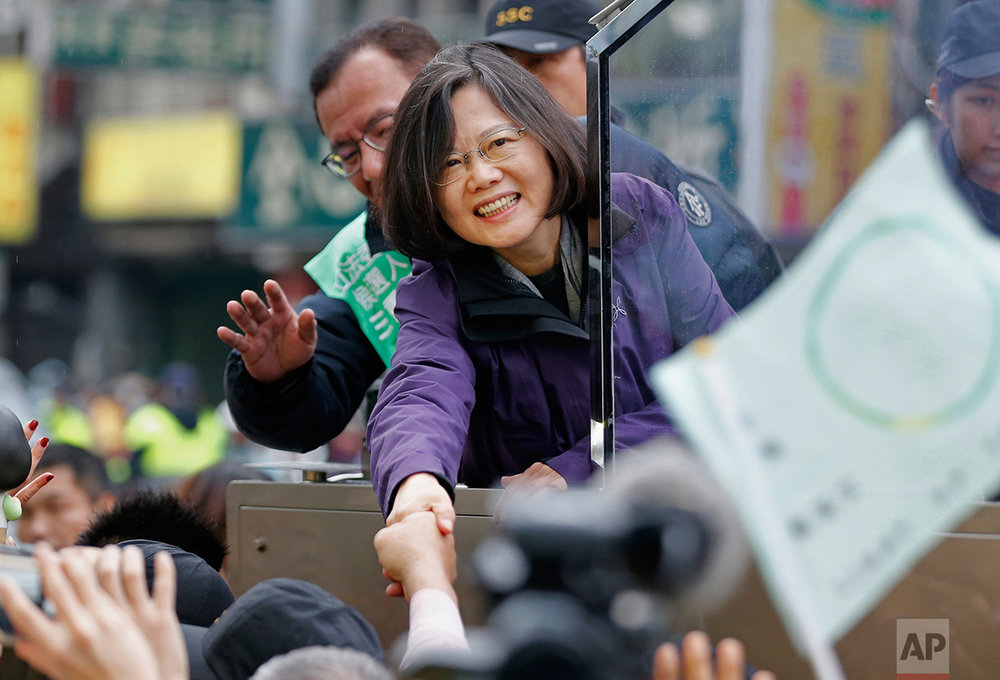 Taiwan's opposition Democratic Progressive Party, DPP, presidential candidate Tsai Ing-wen greets supporters from the back of a truck as she parades through the streets of New Taipei City, Taiwan, Friday, Jan. 15, 2016. Taiwan held its presidential election on Jan. 16, 2016. (AP Photo/Wally Santana)