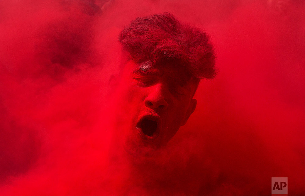 In this Thursday, March 24, 2016, photo, an Indian reveler, face smeared with colored powder, dances during celebrations marking Holi, the Hindu festival of colors, in Gauhati, India. The festival celebrates the arrival of spring. (AP Photo/Anupam Nath)