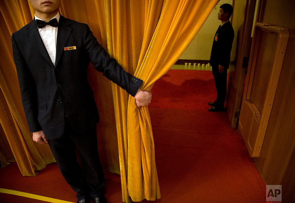 A Chinese usher holds open a curtain during a plenary session of the National People's Congress (NPC) at the Great Hall of the People in Beijing, China, Wednesday, March 9, 2016. (AP Photo/Mark Schiefelbein)