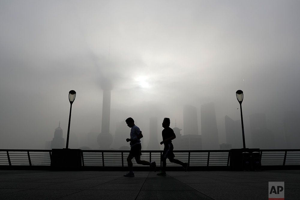 People jog past the Pudong Financial District shrouded with fog and pollution at the Shanghai Bund in Shanghai, China, Thursday, April 14, 2016.  (AP Photo/Andy Wong)
