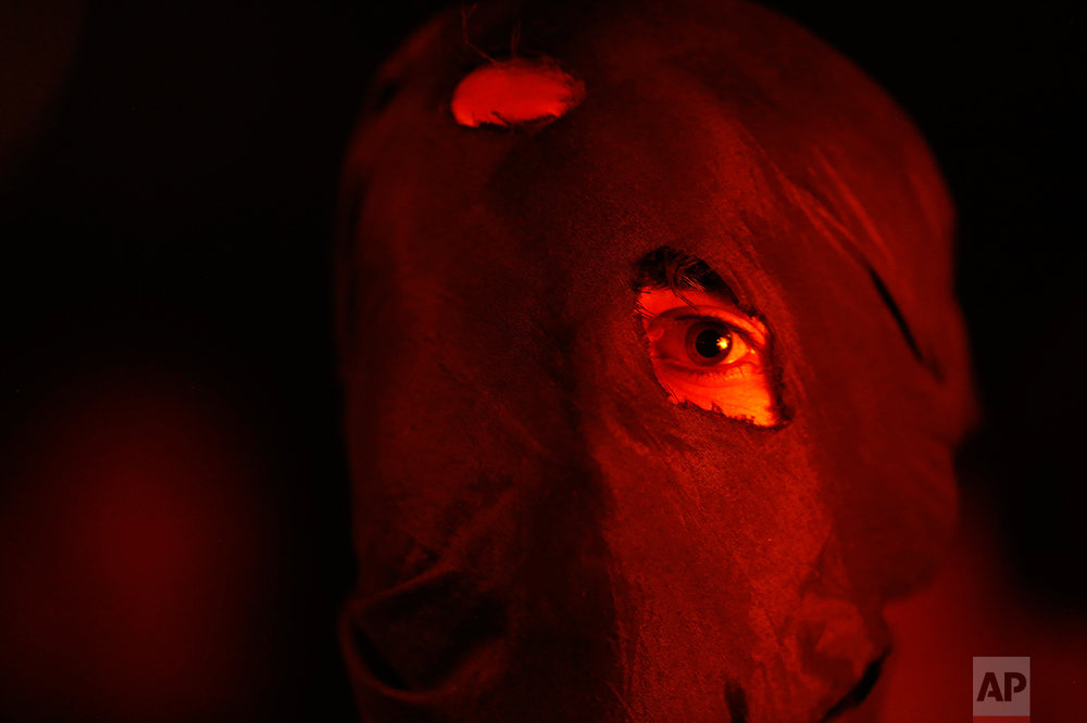 A masked Kashmiri participates in a torch light protest in Srinagar, Indian controlled Kashmir, Thursday, July 21, 2016. (AP Photo/Mukhtar Khan)