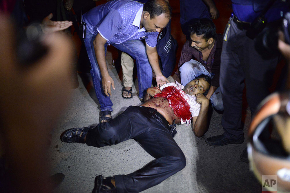 People help an unidentified injured person after a group of gunmen attacked a restaurant popular with foreigners in a diplomatic zone of the Bangladeshi capital Dhaka, Bangladesh, Friday, July 1, 2016. (AP Photo)