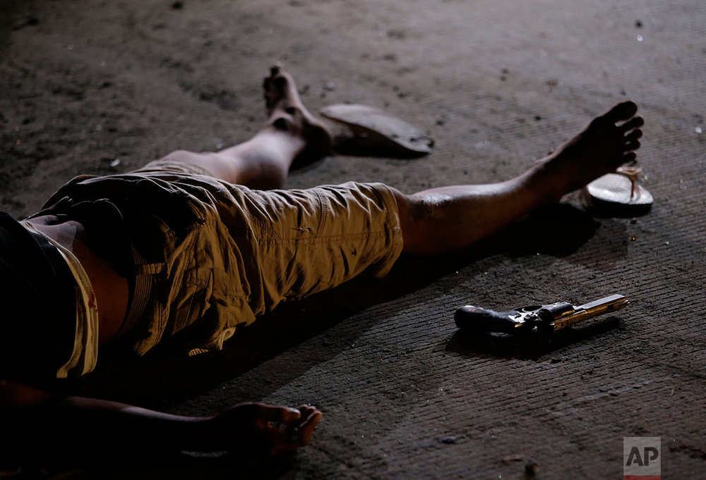 "In this Friday Sept. 6, 2016 photo, an alleged drug suspect lies on the ground beside a gun after he and his companion were killed by police as they tried to evade a checkpoint as part of the continuing ""War on Drugs"" campaign of Philippine President Rodrigo Duterte in Quezon city, north of Manila, Philippines. (AP Photo/Aaron Favila)"