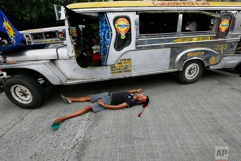 A bloodied protester lies next to a passenger vehicle after he was injured in a violent dispersal outside the U.S. Embassy in Manila, Philippines Wednesday, Oct. 19, 2016. A Philippine police van rammed into protesters, leaving several bloodied, as an anti-U.S. rally turned violent Wednesday at the embassy. (AP Photo/Bullit Marquez)
