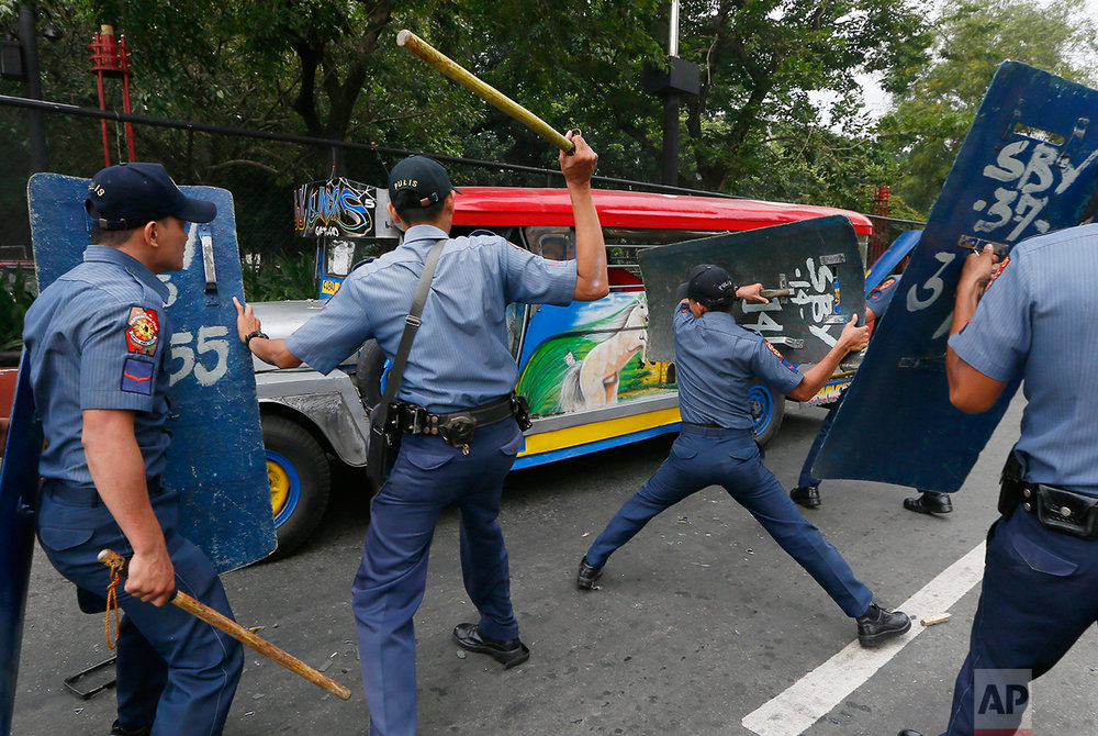 Police officers hit fleeing protesters during a violent dispersal outside the U.S. Embassy in Manila, Philippines Wednesday, Oct. 19, 2016. A Philippine police van rammed into protesters, leaving several bloodied, as an anti-U.S. rally turned violent at the American embassy in Manila. (AP Photo/Bullit Marquez)
