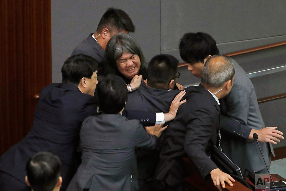 "Newly elected pro-democracy lawmaker Leung Kwok-hung, known as ""Long Hair,"" top center, tries to break through the security guards during the election of president of the Legislative Council in Hong Kong, Wednesday, Oct. 12, 2016.  (AP Photo/Kin Cheung)"