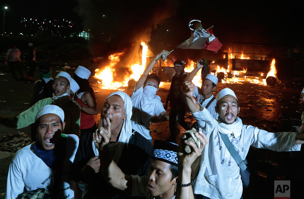 Muslim protesters chant slogans near burning police trucks during a clash with the police outside the presidential palace in Jakarta, Indonesia, Friday, Nov. 4, 2016. (AP Photo/Dita Alangkara)