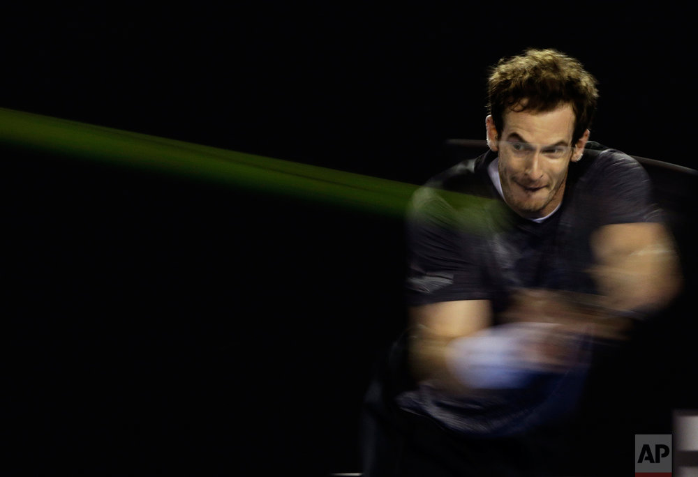 Andy Murray of Britain makes a backhand return to Bernard Tomic of Australia during their fourth round match at the Australian Open tennis championships in Melbourne, Australia, Jan. 25, 2016. (AP Photo/Aaron Favila)