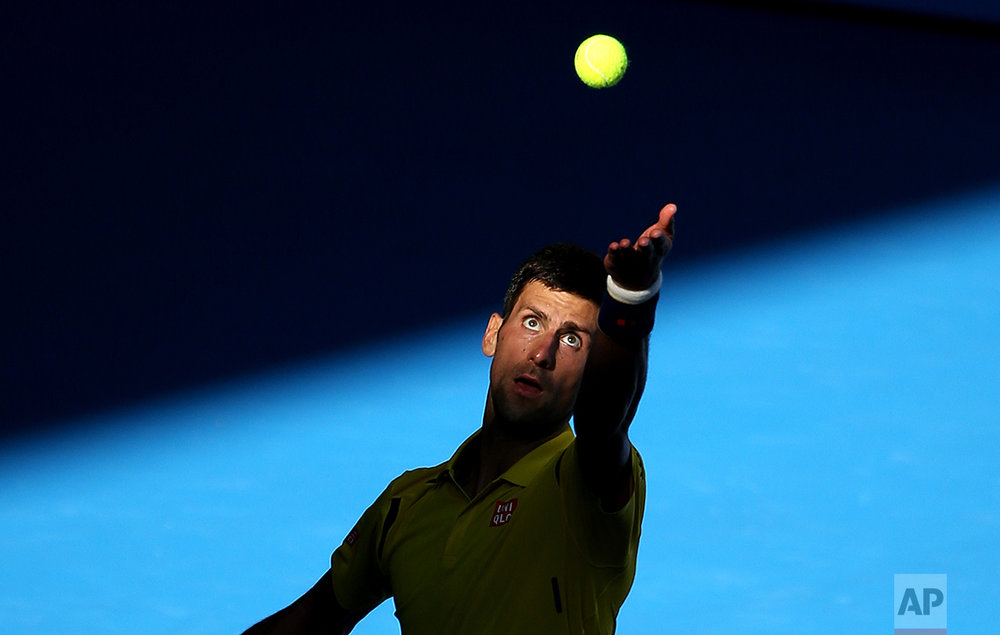 Novak Djokovic of Serbia serves to Gilles Simon of France during their fourth round match at the Australian Open tennis championships in Melbourne, Australia, Sunday, Jan. 24, 2016. (AP Photo/Rick Rycroft)