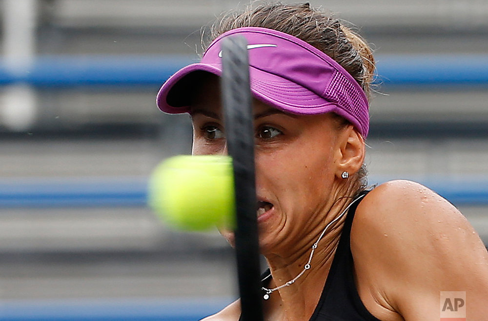 Magda Linette of Poland returns a shot to Viktorija Golubic of Switzerland during their second round match of the Japan Women's Open tennis tournament in Tokyo, Thursday, Sept. 15, 2016. (AP Photo/Shizuo Kambayashi)