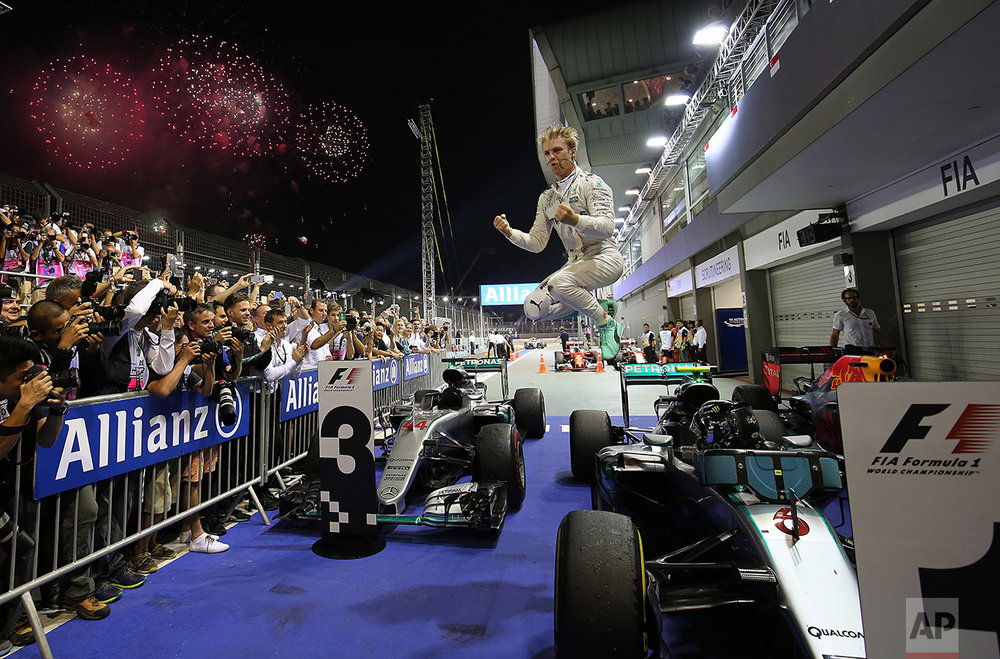 In this Sunday, Sept. 18, 2016 photo, Mercedes driver Nico Rosberg of Germany jumps off his car as he celebrates after winning the Singapore Formula One Grand Prix on the Marina Bay City Circuit Singapore. (AP Photo/Yong Teck Lim)
