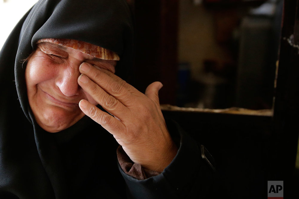 In this Sunday, Dec. 4, 2016 photo, Amina Hamawy cries after she returned to her looted home in the Hanano district of eastern Aleppo, Syria. (AP Photo/Hassan Ammar)