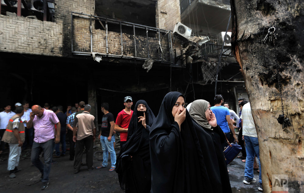Iraqi women wait to hear about family members who went missing after a car bomb hit Karada, a busy shopping district in the center of Baghdad, Iraq, Sunday, July 3, 2016. (AP Photo/Hadi Mizban)