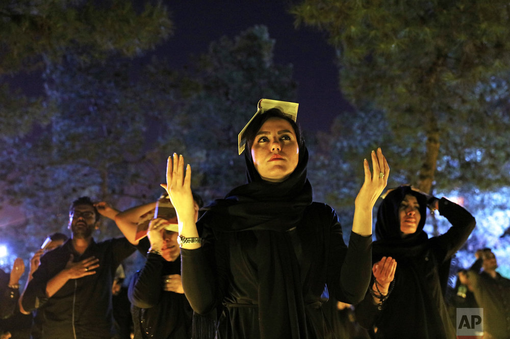 Iranian Shiite Muslims pray as they place the Quran on their heads at the graves of soldiers who were killed during 1980-88 Iran-Iraq War, at the Behesht-e-Zahra cemetery, during the holy fasting month of Ramadan, just outside Tehran, Iran, Monday, June 27, 2016. Iranian Muslims spent the night in prayer and devotion commemorating Laylat Al Qadr, or the Night of Power, which is the anniversary of the night that Muslims believe Prophet Muhammad received the first revelation of the Quran by the angel Gabriel. Ramadan is an Islamic holy month of fasting in which Muslims are expected to abstain from food, drink smoking and sex during daylight and to focus on spirituality, good deeds and charity. (AP Photo/Ebrahim Noroozi)