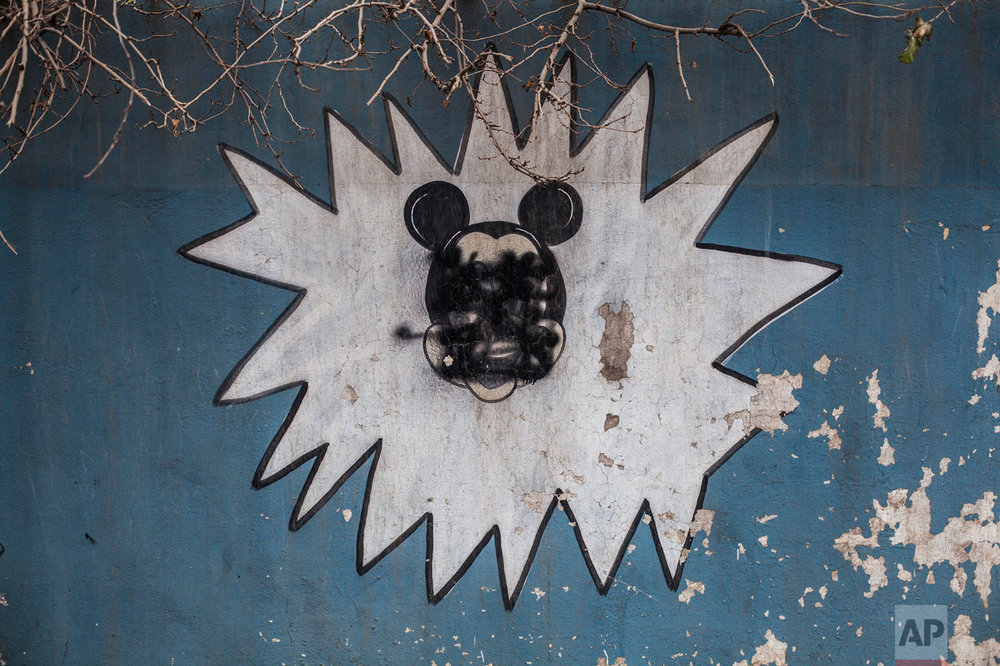This Sunday, Dec. 18, 2016 photo shows a drawing of Mickey Mouse with its face painted over by Islamic States militants on the wall of a kindergarten n the al-Barid district in Mosul, Iraq. (AP Photo/Manu Brabo)