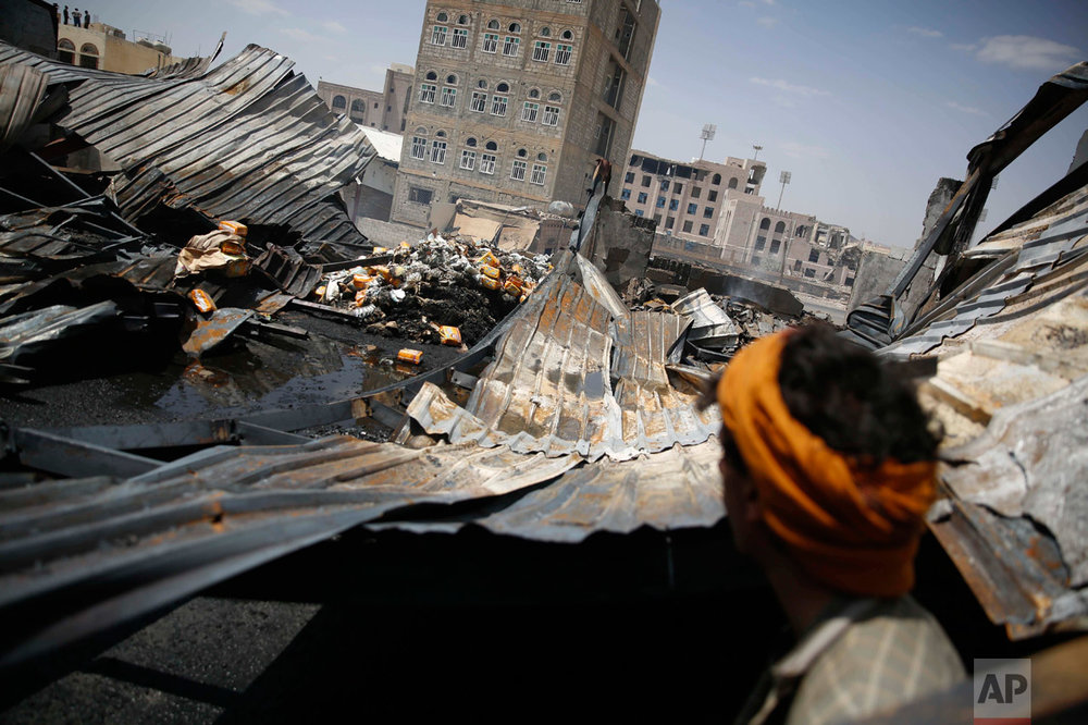 In this Thursday, Sept. 17, 2015, file photo, a worker looks at a chocolate factory destroyed by a Saudi-led airstrike in Sanaa, Yemen. Businesses worth millions of dollars have sustained major destruction in Yemen's year-long conflict either by the Saudi-led coalition targeting Shiite rebels or ground fighting and random shelling by the rival parties, an international rights group said. (AP Photo/Hani Mohammed)