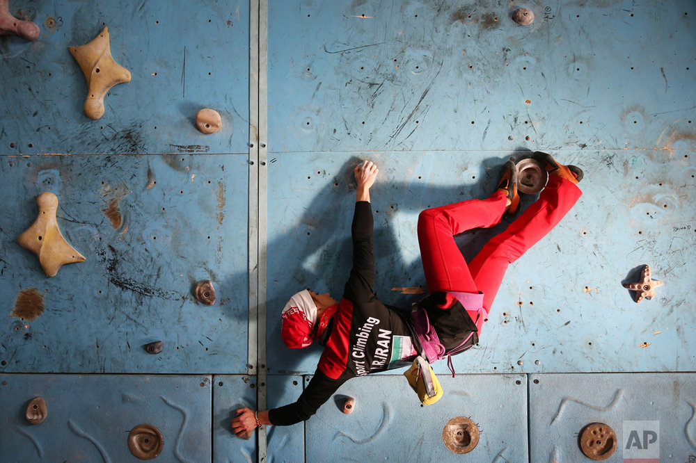 In this Monday, Jan. 18, 2016 photo, Iranian rock climber, Farnaz Esmaeilzadeh, scales a climbing gym in the city of Zanjan, some 330 kilometers (207 miles) west of the capital Tehran, Iran. Esmaeilzadeh, 27, who has been climbing since she was 13, has distinguished herself in international competitions despite the barriers she faces as a female athlete in conservative Iran. (AP Photo/Ebrahim Noroozi)