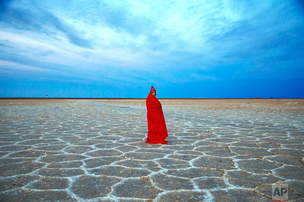 In this picture taken on Thursday, Dec. 1, 2016, an Iranian woman covers herself with a blanket due to the cold, while visiting Khour salt lake during her tour of the Mesr desert about 305 miles (500 kilometers) southeast of the capital Tehran, Iran. Deserts make up parts of Iran which have recently become tourist destinations for young Iranians looking for a break on their weekend. The increase in tourists to the desert has stimulated economic growth in the area. (AP Photo/Ebrahim Noroozi)